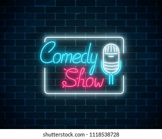 Glowing neon comedy show sign with retro microphone in rectangle frame on a brick wall background.
