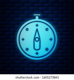 Glowing neon Compass icon isolated on brick wall background. Windrose navigation symbol. Wind rose sign.