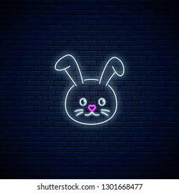 Glowing neon sign of cute rabbit in kawaii style on dark brick wall background. Cartoo happy smiling bunny in neon style