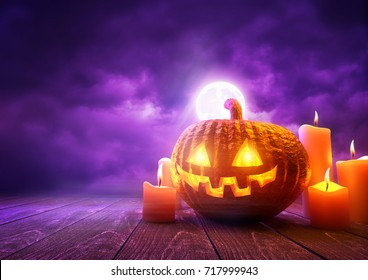 A glowing Pumpkin Jack-O-Lantern against purple sky background on Halloween, mixed media illustration.