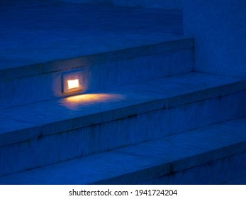 Glowing rectangular light fixture on riser illuminates small part of one step near top of outdoor concrete stairway at dusk, with digital painting effect. 3D rendering.