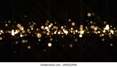 Gold light bokeh sparks, golden glitter shine. Shiny bright snow bokeh blur effect, shimmering dust light and magic glow sparkles, Christmas luxury background