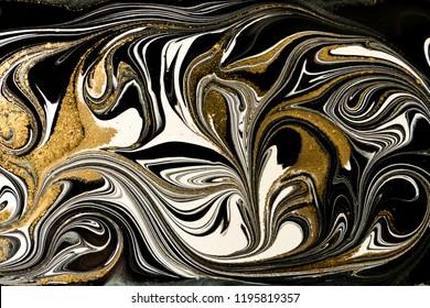 Gold marbling texture design. Black and golden marble pattern. Fluid art.