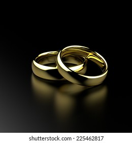 Gold wedding rings on black grained background.