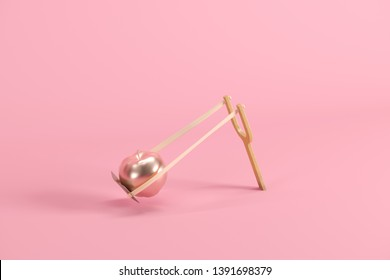 Golden apple in a slingshot on pink background. Minimal fruit idea concept. 3D render.