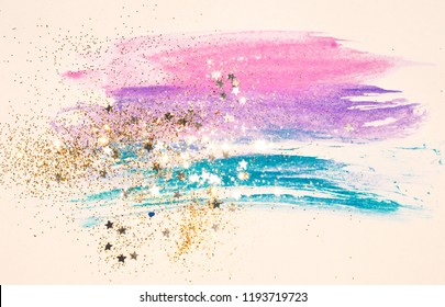 Golden glitter and glittering stars on abstract watercolor splash in vintage nostalgic colors.