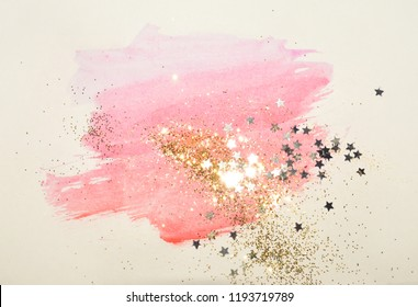 Golden glitter and glittering stars on abstract pink watercolor splash in vintage nostalgic colors.