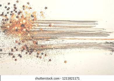 Golden glitter and glittering stars on abstract black and gold watercolor splashes in vintage nostalgic colors.