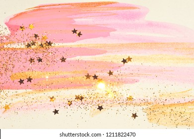 Golden glitter and glittering stars on abstract pink and gold watercolor splashes in vintage nostalgic colors.