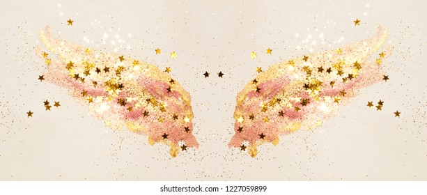 Golden glitter and glittering stars on abstract pink watercolor wings in vintage nostalgic colors.