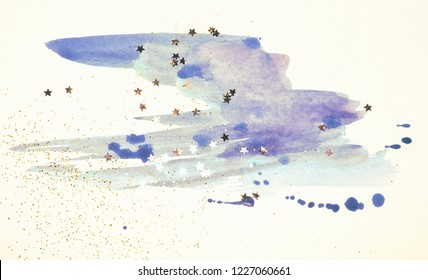 Golden glitter and glittering stars on abstract blue watercolor splash in vintage nostalgic colors.