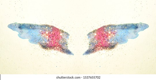 Golden glitter on abstract pink and blue watercolor wings in vintage nostalgic colors.