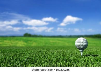 Golfball auf Tee auf grünem Gras