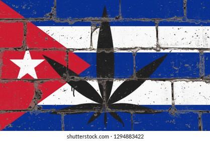 Graffiti street art spray drawing on stencil. Cannabis leaf symbol on brick wall with flag Cuba