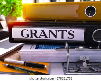 Grants - Black Ring Binder on Office Desktop with Office Supplies and Modern Laptop. Grants Business Concept on Blurred Background. Grants - Toned Illustration. 3D Render.