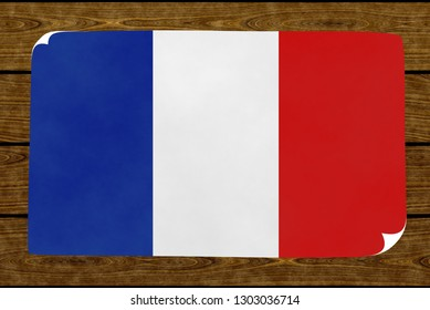 Graphic illustration of a French flag painted on the paper pasted on the woody wall