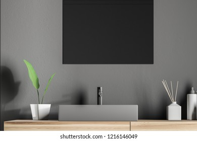 Gray angular bathroom sink standing on wooden countertop with rectangular mirror above it in gray wall room. 3d rendering