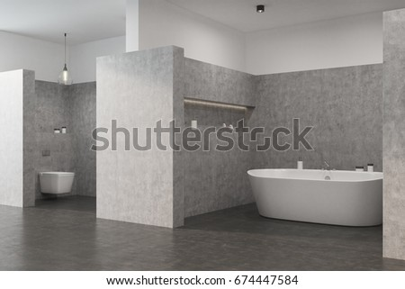 Gray bathroom interior with a concrete floor, a white tub, a toilet and an