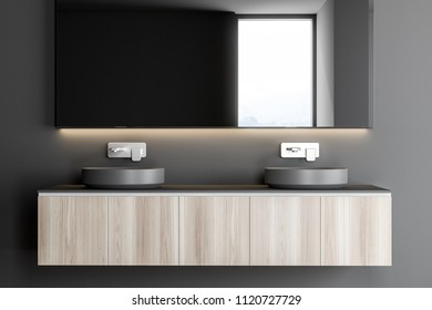 Gray double sink standing on a wooden countertop attached to a gray wall. A long horizontal mirror hanging above it. 3d rendering mock up