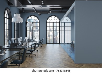 Gray open space office interior with arch like windows, a wooden floor and a row of computer tables. 3d rendering mock up