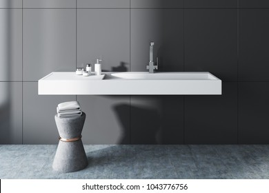 Gray wall bathroom interior with a long white sink and a chair with towels. A front view. 3d rendering