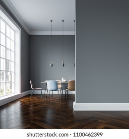 Gray wall dining room interior with a wooden floor, a table with several types of pastel color chairs standing around it and a row of lamps hanging above it. Mock up wall 3d rendering mock up