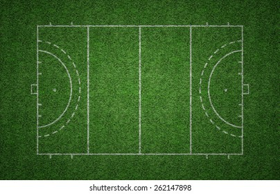 Green grass pitch of field hockey with white lines marking the pitch.