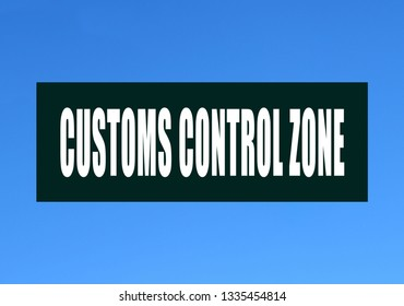 """A green sign with an inscription in English: """"Customs control zone"""" against a blue sky. Storage customs clearance."""