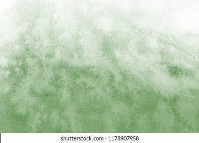 Green watercolor ombre leaks and splashes texture on white watercolor paper background. Natural organic shapes and design.