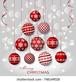 Greeting card with red Christmas balls. Holiday decorations on silver bokeh background.