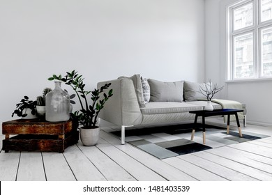 Grey couch behind small black coffee table atop white floorboards and square rug in luxury living room