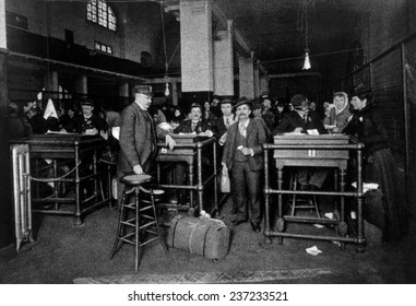 A group of immigrants showing passports, money, and answering questions prior to final discharge into the United States, Ellis Island, c.1902.