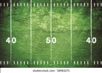 Grunge football field with close up of midfield and white chalk drawn lines.