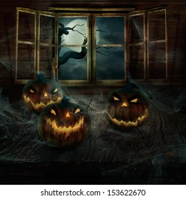 Halloween Design - Abandoned pumpkins.Holiday horror background with  Pumpkins, spider webs, and full moon with spooky tree