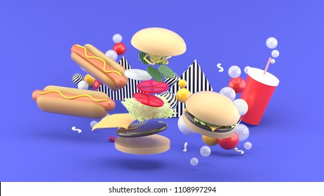 Hamburgers, hot dogs and soft drinks among colorful balls on a purple background.-3d rendering.