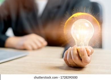Hand der Geschäftsfrau, die die beleuchtete Glühbirnendecke mit der Partikelkugelwelt und der gelben Lichtlinie , Idee, Innovation und Inspiration Konzept, kopieren Raum. 3D-Darstellung