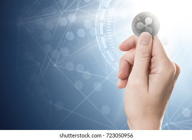 Hand holding a silver Ripple coin on a bright background with blockchain network. Copy space included. 3D rendering