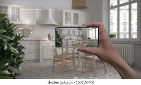 Hand holding smart phone, AR application, simulate furniture and interior design products in real home, architect designer concept, blur background, retro living room with kitchen, 3d illustration
