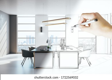 Hand with pen drawing luxury coworking office with computers on table and megapolis city view. Workplace and corporate concept.