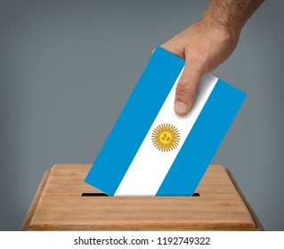 Hand putting a voting ballot  with the colors of the flag of Argentina into the box.