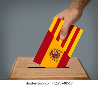 Hand putting  voting ballot  with the colors of Spain and Catalonia into the box.