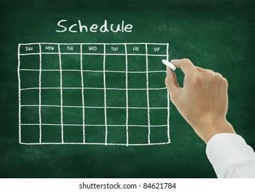 Hand writing schedule on chalkboard