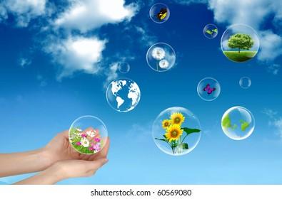 Hands holding bubbles against a blue sky