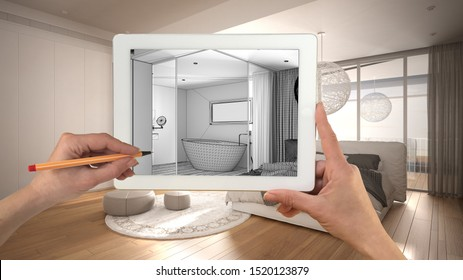 Hands holding and drawing on tablet showing modern white bedroom with bathroom details CAD sketch. Real finished interior in the background, architecture design presentation, 3d illustration