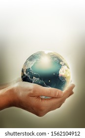 Hands holding earth - conceptual image of the earth day, saving energy, protecting the environment. Elements of this image furnished by NASA
