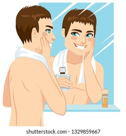Handsome man applying after shave in his face in front of mirror