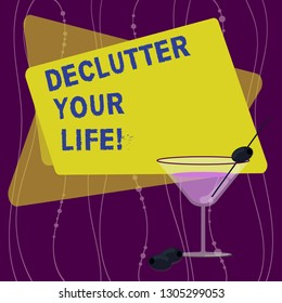Handwriting text Declutter Your Life. Concept meaning remove unnecessary items from untidy overcrowded place Filled Cocktail Wine Glass with Olive on the Rim Blank Color Text Space.