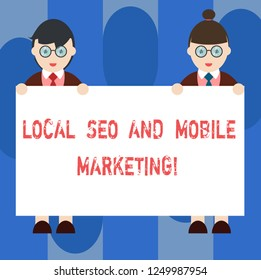 Handwriting text Local Seo And Mobile Marketing. Concept meaning Search engine optimization Digital promotion Male and Female in Uniform Standing Holding Blank Placard Banner Text Space.