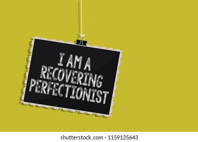 Handwriting text I Am A Recovering Perfectionist. Concept meaning Obsessive compulsive disorder recovery Hanging blackboard message communication information sign yellow background.