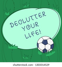 Handwriting text writing Declutter Your Life. Concept meaning remove unnecessary items from untidy overcrowded place Soccer Ball on the Grass and Blank Outlined Round Color Shape photo.